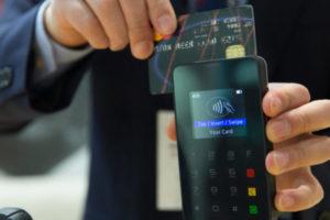 a man swiping his bank card through an eftopos machine