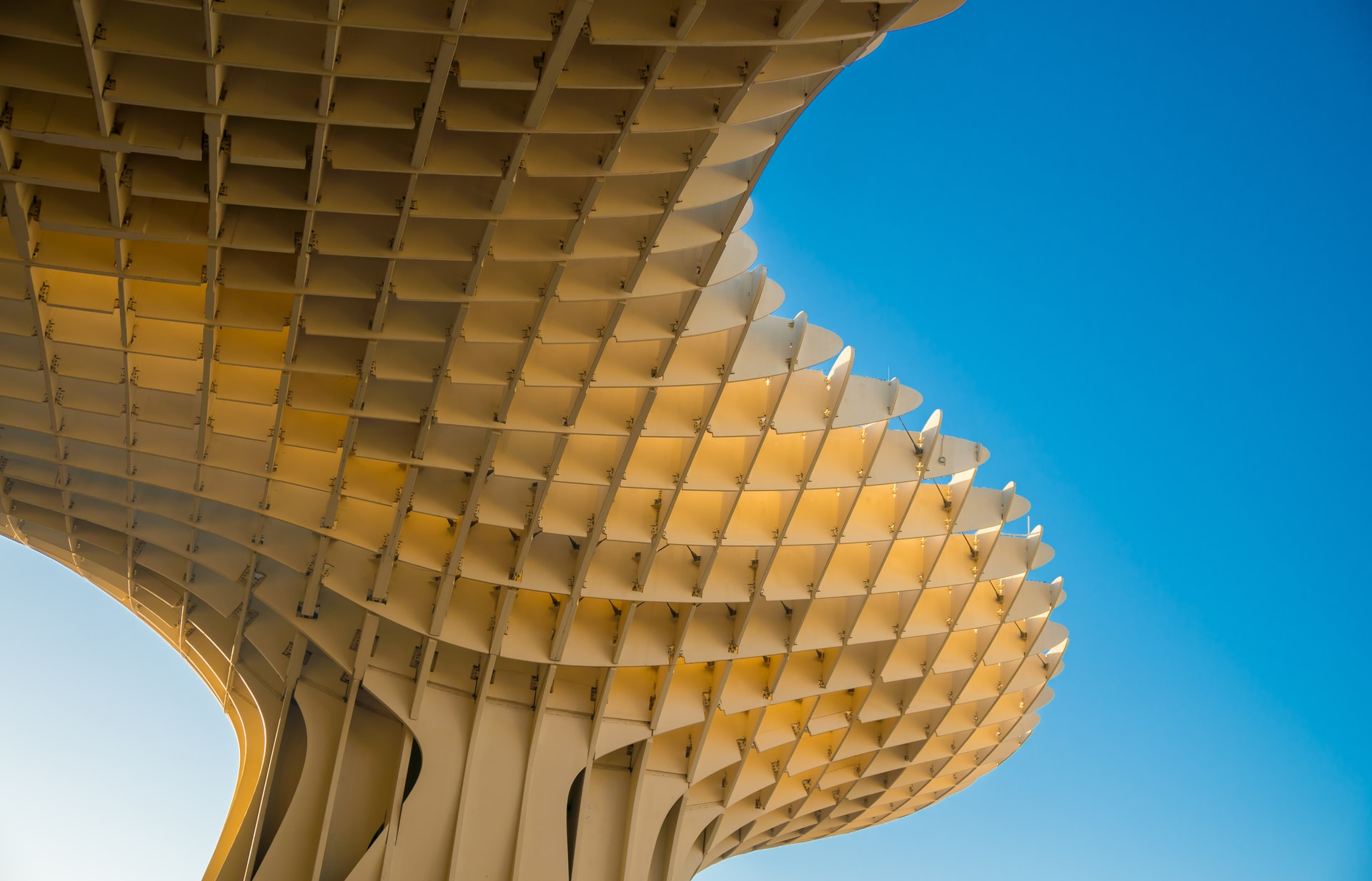 a close up of a large abstract architectural pattern that looks like honeycomb with blue sky in the background