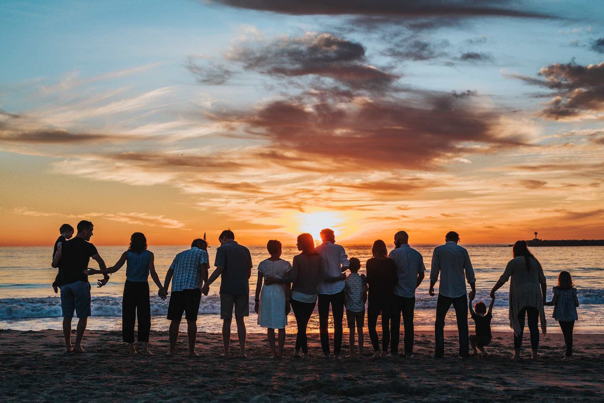 group of people on beach at sunset holding hands